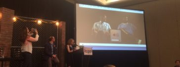 Nigel Poor, left, shoots a video during her Podquest finalists' presentation at Podcast Movement 2016 in Chicago. On the screen are Earlonne Woods and Antwan Williams, Poor's partners in producing the Ear Hustle podcast.