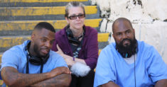 The three producers of the Ear Hustle podcast sit on stairs at San Quentin Prison in California.